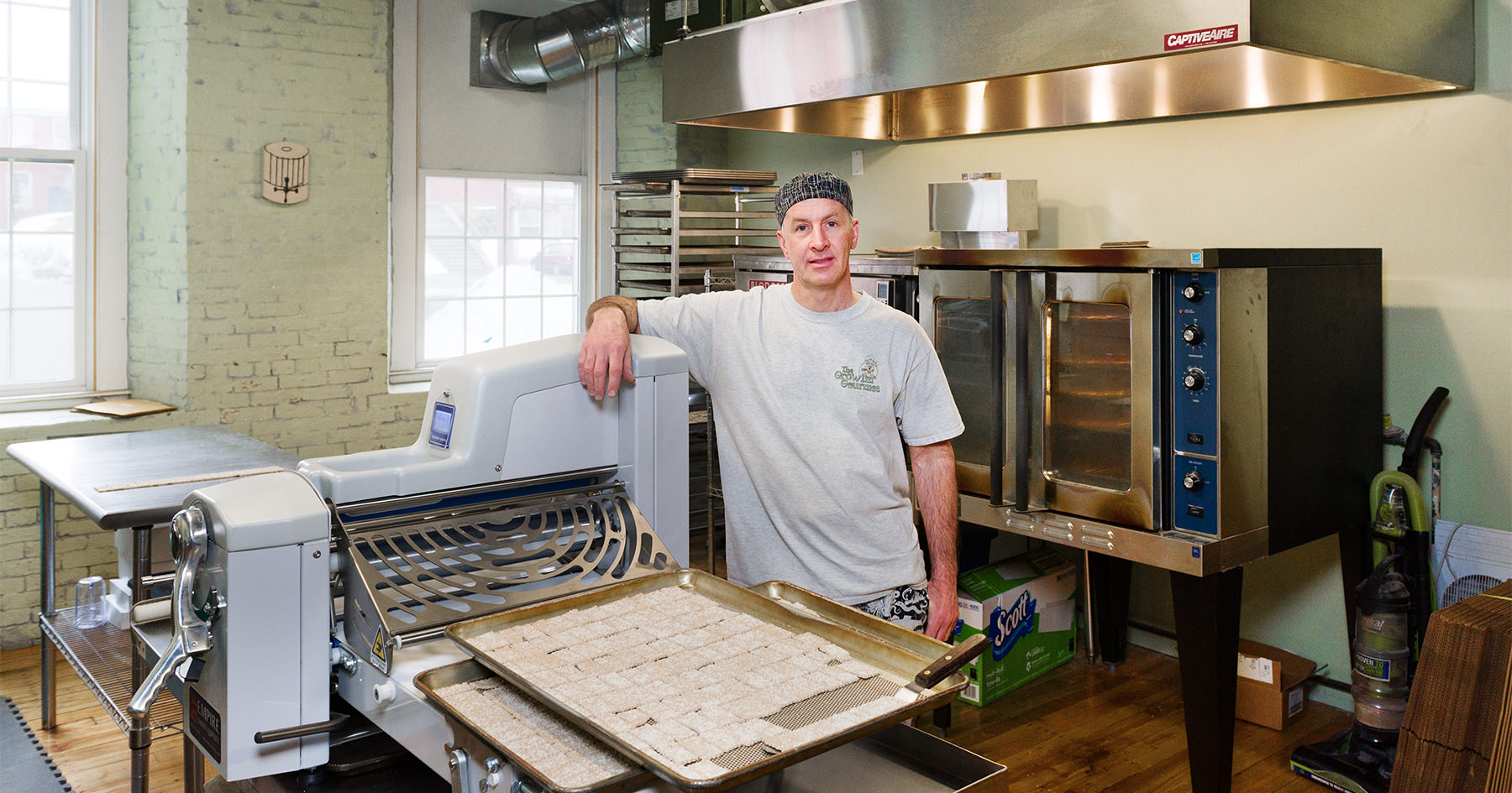 Steve Harmon, chef and owner of Growlin Gourmet stands next to a fresh batch of dog treats in his kitchen at the Pepperell Mill Campus, photographed by Portland Headshot.