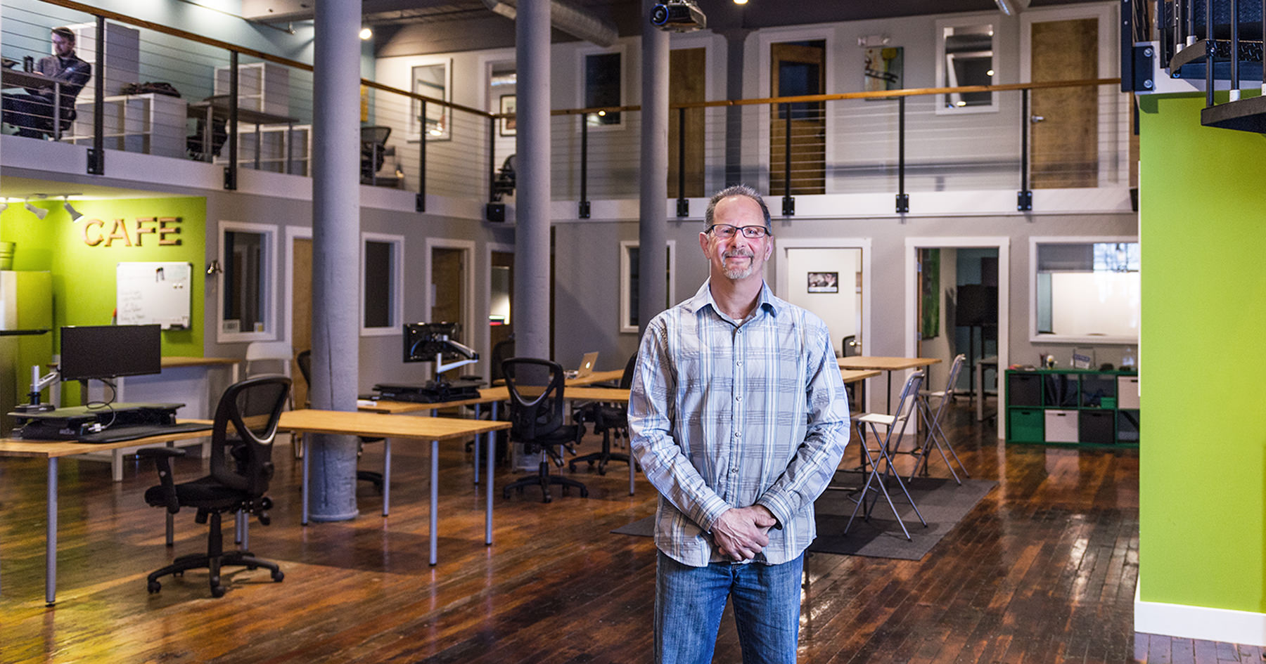 Marc Feldman standing in the welcoming coworking space near the lobby of the Pepperell Mill Campus, Building 13, photographed by Portland Headshot