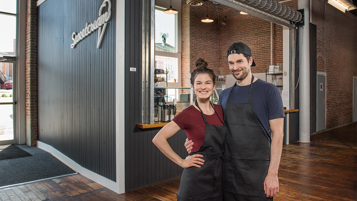 Jackie and Jon, just before their wedding, standing in front of their venture together, making homemade ice cream at Sweetcream Dairy in the Pepperell Mill Campus. Photograph by Portland Headshot